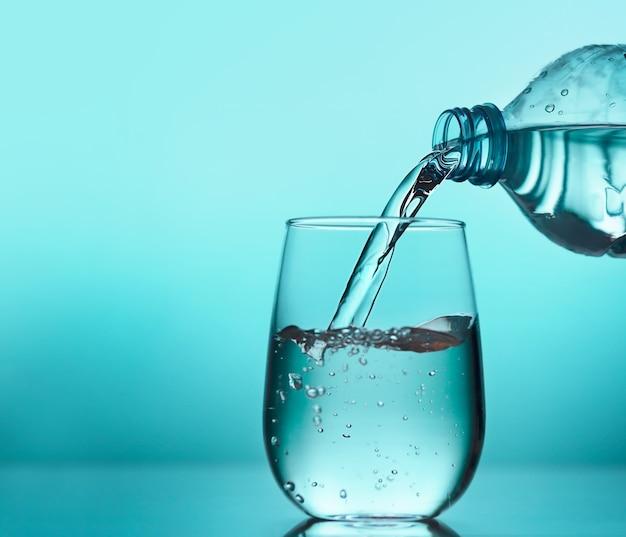 Acqua fresca che versa dalla bottiglia di plastica in un bicchiere su sfondo blu. bere acqua ogni giorno è importante per una salute ottimale