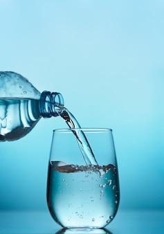Acqua fresca che versa dalla bottiglia di plastica in un bicchiere su sfondo blu, orientamento verticale