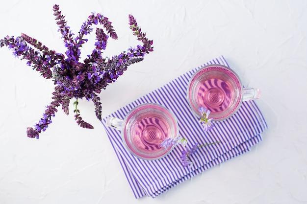 Acqua fresca con lavanda in bicchieri e un mazzo di fiori in una brocca sul tavolo. cocktail aromatico alla lavanda. copia spazio. vista dall'alto