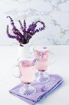 Acqua fresca con lavanda in bicchieri e un mazzo di fiori in una brocca sul tavolo. cocktail aromatico alla lavanda. copia spazio. vista verticale