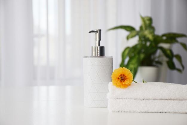 Asciugamani bianchi freschi piegati sul tavolo bianco, fiori d'arancio e contenitore di sapone liquido con foglie verdi di pianta della casa