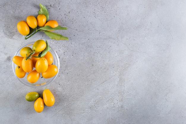 Frutti di cumquat di agrumi interi freschi con foglie poste in una ciotola
