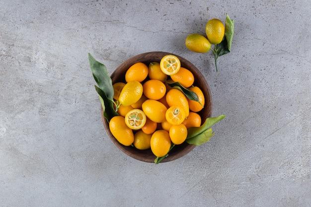 Frutti di cumquat di agrumi freschi interi e affettati con foglie poste in una ciotola di legno