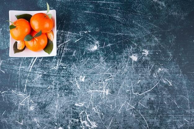 Frutti di mandarino intero fresco con foglie poste in un piatto bianco.