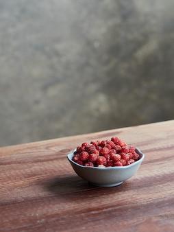 Fragoline di bosco fresche in una piccola ciotola su un tavolo di legno. fragaria vesca