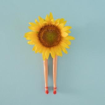 Girasole giallo fresco e gambe di bambola sullo sfondo pastello blu. giardinaggio estivo giungla tropicale arte astratta