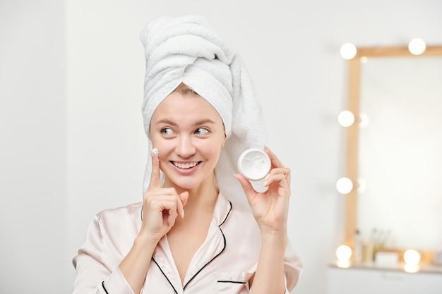 Giovane bella donna fresca con l'asciugamano bianco sulla testa che applica la sua crema idratante facciale sulla guancia dopo la pulizia del viso