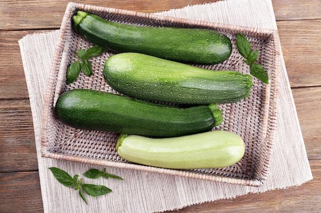 Zucchine fresche con zucca e basilico su vassoio di vimini da vicino