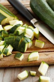 Zucchine fresche su una tavola di legno con un coltello