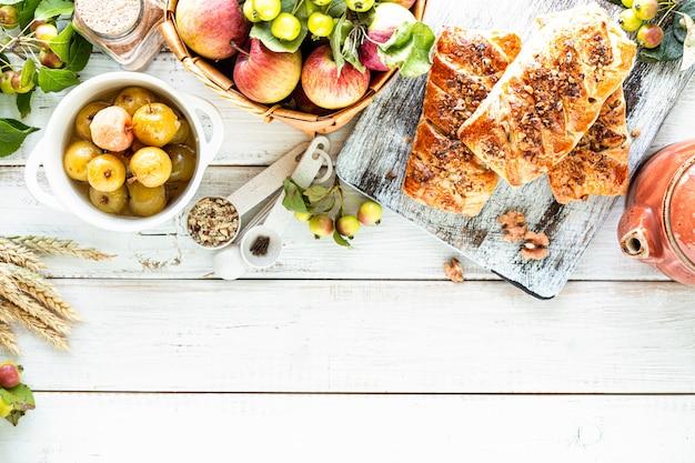 Mele appena sfornate e panini alla cannella a base di pasta sfoglia su un tavolo di legno bianco