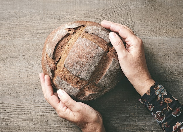 Pane artigianale appena sfornato e mani umane su un tavolo da cucina in legno rustico, vista dall'alto, immagine tonica