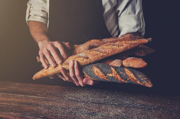 Baguette appena sfornate tengono le mani di un uomo sullo sfondo di un tavolo di legno, foto tonificata