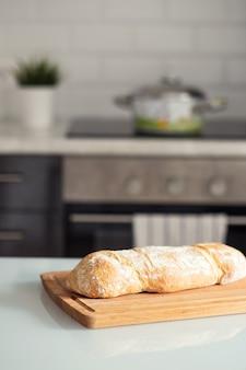 Il pane appena sfornato giace sul tagliere in cucina