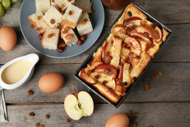 Budino di pane appena sfornato in casseruola e ingredienti su tavola di legno