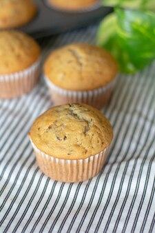 Muffin alla banana con gocce di cioccolato appena sfornate sullo sfondo