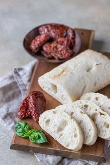 Pane appena sfornato ciabatta sul piatto di legno con pomodori secchi e basilico.