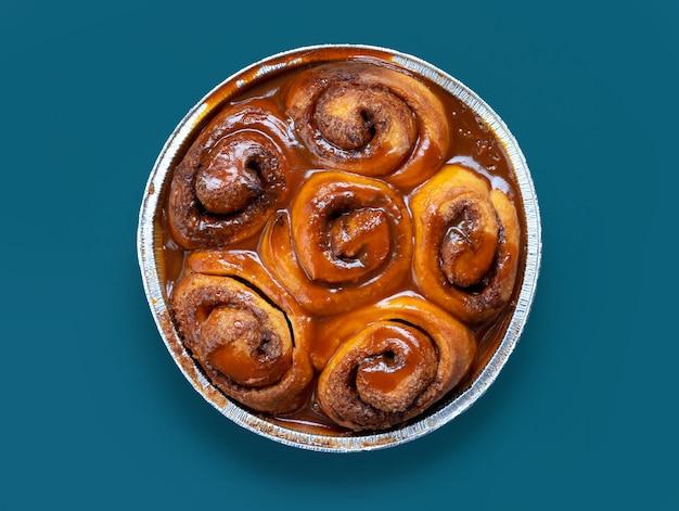 Panini alla cannella appena sfornati ricoperti di salsa al caramello su sfondo blu, vista dall'alto