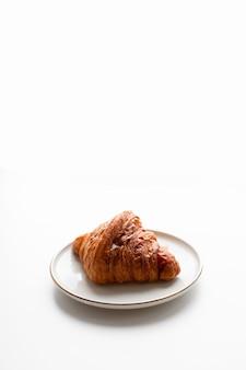 Croissant appena sfornato con ripieno di caramello sulla piastra sulla superficie bianca