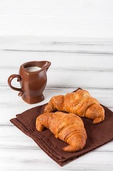 Croissant di recente al forno sul tovagliolo marrone, crema in brocca di latte ceramica su vecchio fondo di legno bianco. dolci freschi a colazione delizioso dessert fotografia del primo piano banner verticale