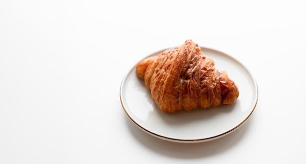 Croissant appena sfornati con caramello sulla piastra isolata su sfondo bianco