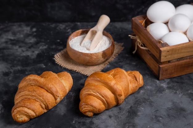 Croissant appena sfornati con uova di gallina e ciotola di farina in legno.