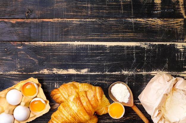 Croissant appena sfornati con farina, cucchiaio di legno, uova e tuorli d'uovo