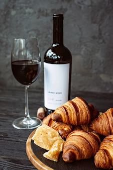 Croissant fragranti appena sfornati con formaggio a pasta dura su una tavola di pietra nera, un bicchiere di vino rosso e una bottiglia. cena romantica.