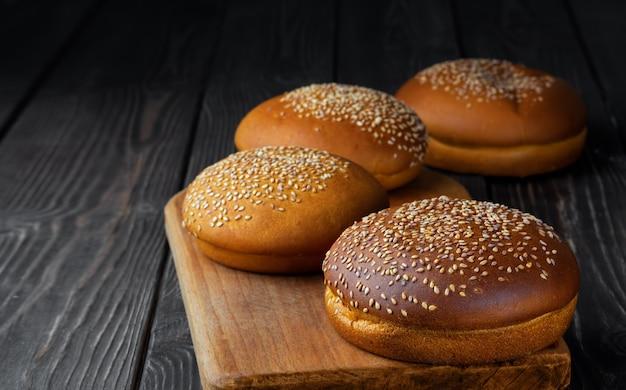 Panini di hamburger di recente cotti con sesamo su superficie di legno scura