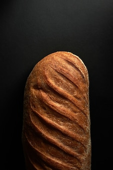 Pane bianco sano appena sfornato su sfondo nero con spazio di copia. vista dall'alto