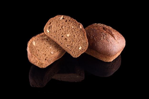 Pane fatto in casa appena sfornato isolato sul nero. tagliare a metà il pane di segale con le noci. mangiare sano e panetteria tradizionale, concetto di pane da forno.
