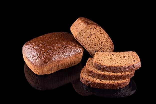 Pane fatto in casa appena sfornato isolato sul nero. tagliare a metà il pane di segale con le fette. mangiare sano e panetteria tradizionale, concetto di pane da forno.