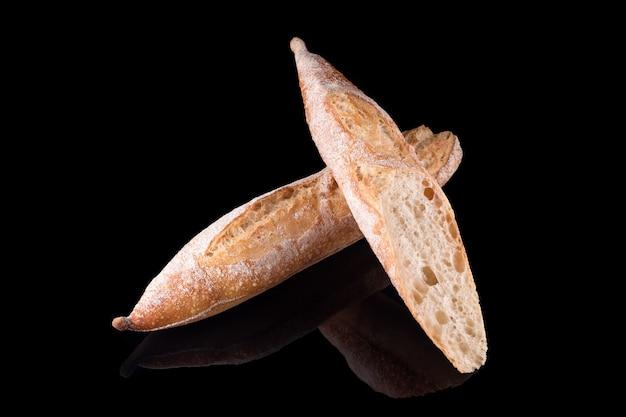 Pane fatto in casa appena sfornato isolato sul nero. baguette di pane francese. mangiare sano e panetteria tradizionale, concetto di pane da forno.
