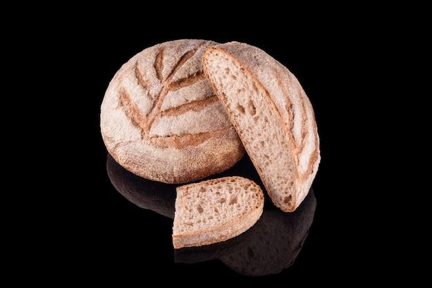 Pane fatto in casa appena sfornato isolato sul nero. pane di segale fresco. mangiare sano e panetteria tradizionale, concetto di pane da forno.