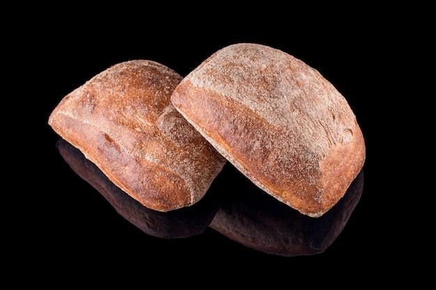 Pane fatto in casa appena sfornato isolato sul nero. pane ciabatta italiano. mangiare sano e panetteria tradizionale, concetto di pane da forno.