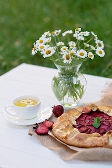 Galette fatta in casa appena sfornata o torta di fragole aperta e foglie di menta fresca con una tazza di tisana di camomilla