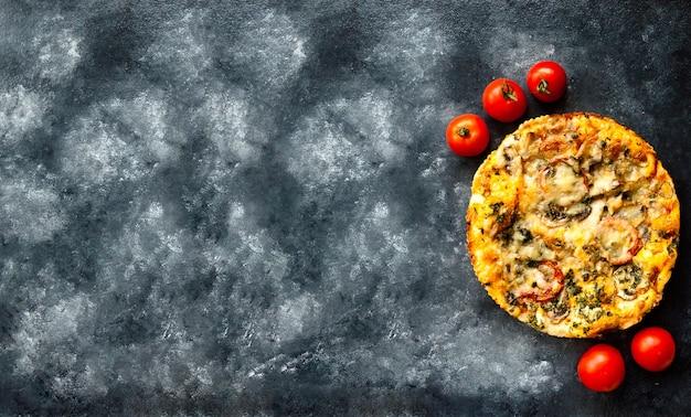 Pizza calda italiana fatta in casa appena sfornata con funghi, mozzarella e pomodoro su un tavolo di cemento nero .e vista dall'alto. avvicinamento. messa a fuoco selettiva. copia spazio.