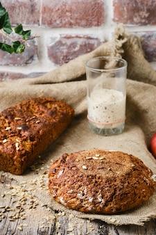 Pane a lievitazione naturale fatto in casa appena sfornato. pane di segale e farina di grano tenero, lievito naturale in un bicchiere accanto al tavolo. idea per la ricetta e la cottura del pane naturale e sano
