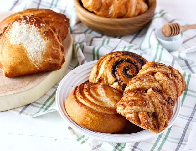Panini dolci fatti in casa appena sfornati con semi di papavero e miele sul tavolo in piattino a bordo e ciotola di legno