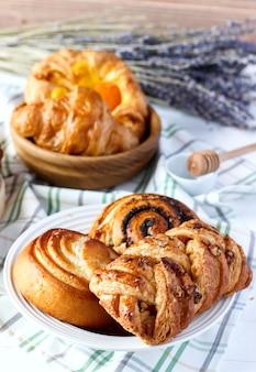 Panini dolci fatti in casa appena sfornati con semi di papavero e miele sul tavolo in piattino