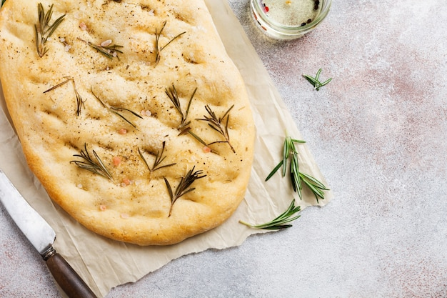 Cottura del pane focaccia casalinga tradizionale italiana appena sfornata con condimenti e rosmarino su carta pergamena e sfondo grigio chiaro. vista dall'alto.