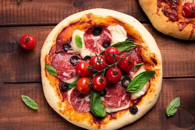 Pizza appena sfornata con pomodori e basilico su una tavola di legno