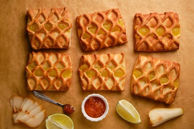 Mini torte di pasta sfoglia appena sfornate con ripieno di marmellata di pere e lime su pergamena con fresca con fette di pera e lime, vista orizzontale dall'alto, flatlay