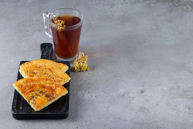 Pane piatto affettato appena sfornato con semi neri con una tazza di vetro di tisana