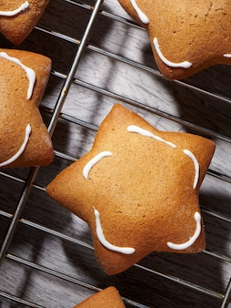 Biscotti ginder a forma di stella appena sfornati sulla griglia di raffreddamento. primo piano, vista dall'alto.