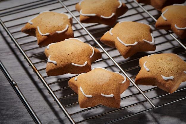 Biscotti di zenzero a forma di stella appena sfornati sulla griglia di raffreddamento. primo piano, vista del fuoco selettivo
