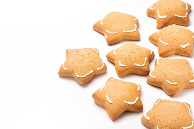 Biscotti di zenzero a forma di stella appena sfornati isolati su priorità bassa bianca. primo piano, vista del fuoco selettivo