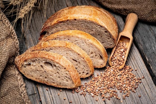 Pane tradizionale appena sfornato sulla tavola di legno. pane rustico con grano saraceno e prugne