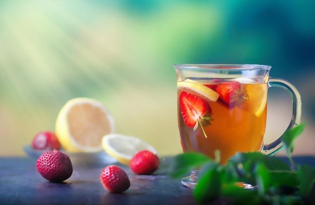 Tè appena preparato con limone e fragole in una grande tazza di vetro