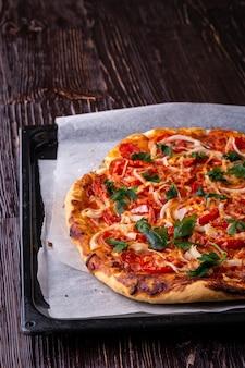 Pizza calda appena cotta e fetta con formaggio prosciutto carne pomodoro cipolla prezzemolo fatto in casa