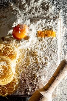 La pasta appena cotta giace su una superficie scura spolverata di farina. pasta italiana. tagliatelle. pasta cruda. ricetta pasta italiana. vista dall'alto, copia dello spazio.